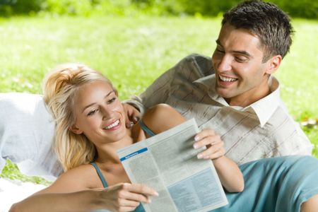 Young happy couple reading together newspaper outdoors Stock Photo - 6546203