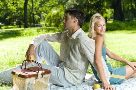 Young happy amorous couple together at picnic, outdoors photo