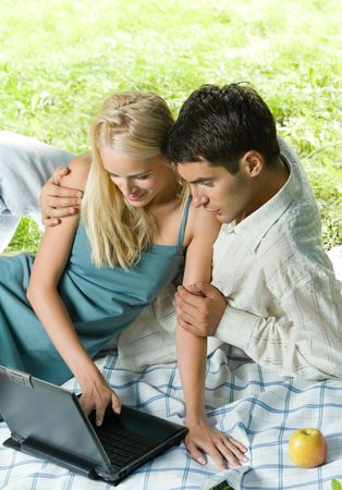 Young happy couple using laptop together, outdoors photo