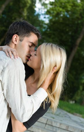 Young happy amorous couple kissing, outdoors photo