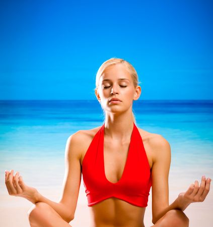 Woman doing yoga moves or meditating on beach photo