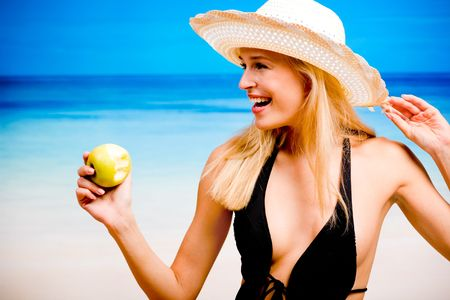 blonde bikini: Young smiling woman with apple on the beach