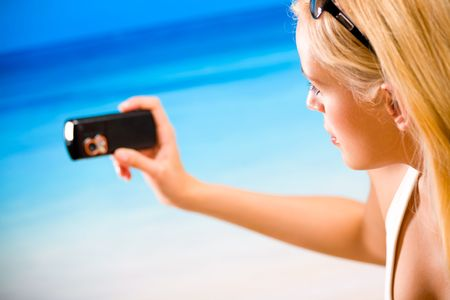 Woman taking photograph by cell phone on beach photo