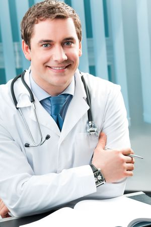 Happy smiling doctor with pen at office photo