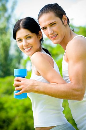 woman working out: Young happy couple exercising with dumbbell, outdoors