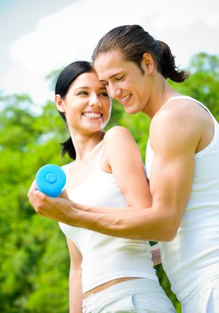 Young happy couple exercising with dumbbell, outdoors photo