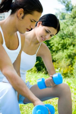Young happy couple exercising with dumbbell, outdoors. Focus on woman photo