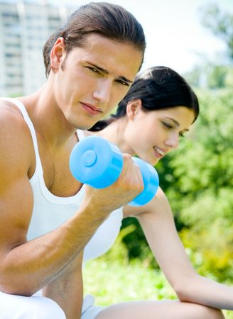Young happy couple exercising with dumbbell, outdoors. Focus on man photo