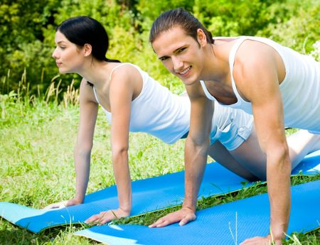 horizont: Young happy couple doing fitness exercises together outdoor. Focus on man.