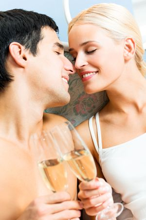 Young happy amorous couple with champagne at bedroom photo