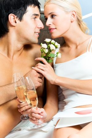 Young happy amorous couple with champagne at bedroom Stock Photo - 6818257