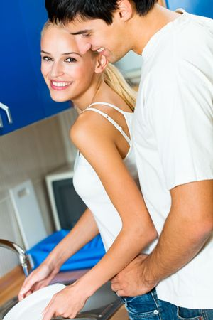 Portrait of young happy amorous embracing couple at home photo