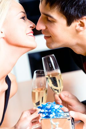 Kissing couple on romantic date or celebrating together at restaurant photo
