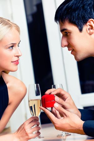 Happy amorous couple and a special man proposal in restaurant photo