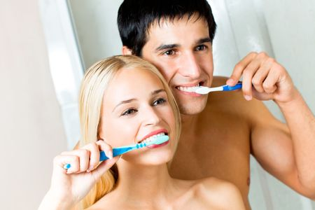 Young couple cleaning teeth together at bathroom photo