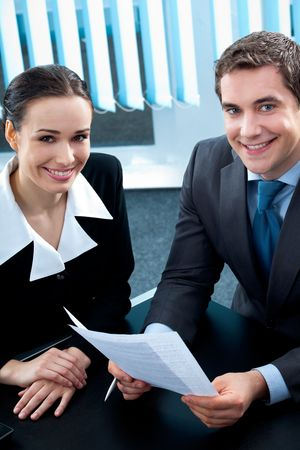 Businesspeople or business person and client, with document at office photo
