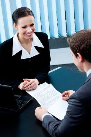 interview job: Dos de los empresarios, o la empresaria y el cliente, con el documento en la Oficina Foto de archivo