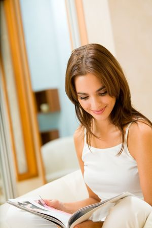 Young happy woman reading magazine at home photo