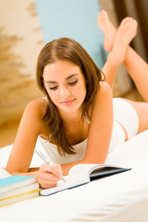 Young woman with notebook or organizer at home photo