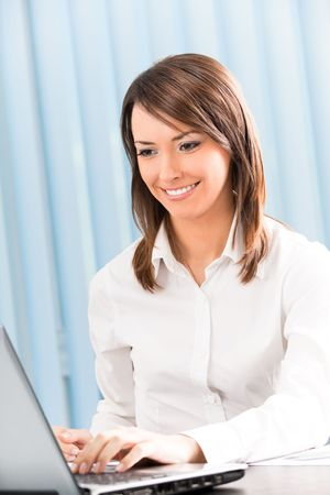 Happy businesswoman working with laptop at office photo