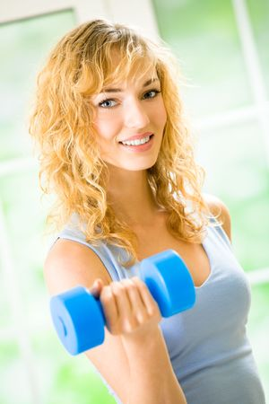 Young happy woman exercising with dumbbell at home Stock Photo - 7123125