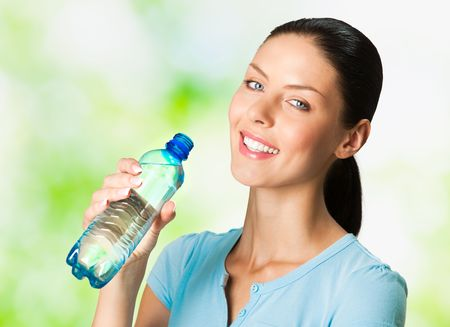 Young smiling woman with bottle of water, outdoors Stock Photo - 7268995