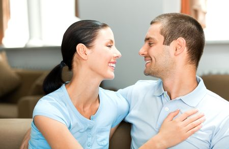Young happy smiling attractive couple at home photo