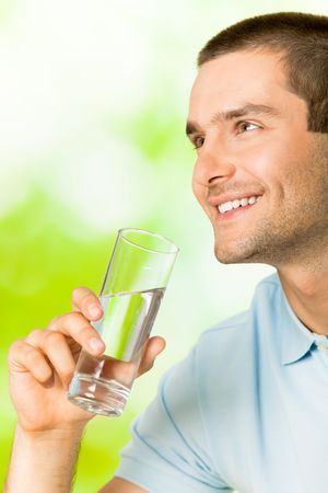 Young smiling man with glass of water, outdoors Stock Photo - 7354805