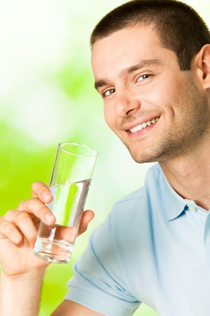 man drinking water: Young smiling man with glass of water, outdoors