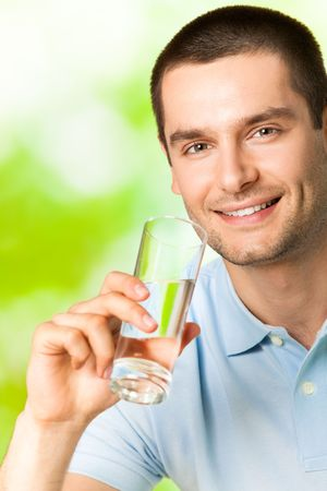 1 man only: Young smiling man with glass of water, outdoors
