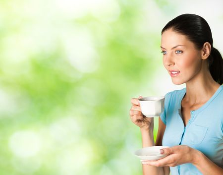 Young happy smiling woman drinking coffee, outdoors. To provide maximum quality, I have made this image, by combination of two photos. You can use left part for slogan, big text or banner. photo