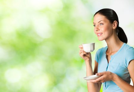 csak a nők: Young happy smiling woman drinking coffee, outdoors. To provide maximum quality, I have made this image, by combination of two photos. You can use left part for slogan, big text or banner. Stock fotó