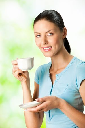 Young happy smiling woman drinking coffee, outdoors photo