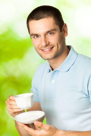 hombre tomando cafe: Hombre sonriente joven feliz beber caf�, al aire libre