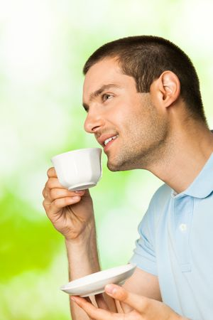 Young happy smiling man drinking coffee, outdoors photo