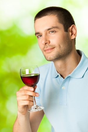 vertical wellness: Young man with glass of redwine, outdoors
