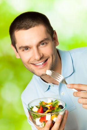 man eten: Jonge gelukkig lachend man eten salade, buitenshuis