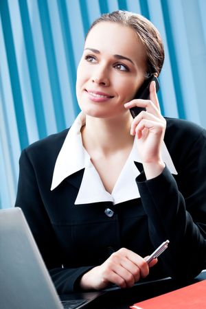 Successful businesswoman with cellphone and laptop at office photo