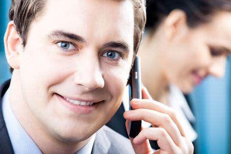 Successful businessman with cellphone and colleague, at office Stock Photo