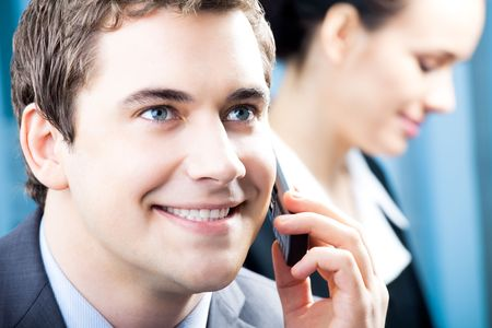 Successful businessman with cellphone and colleague, at office photo