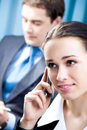 Successful businesswoman with cellphone and colleague, at office photo