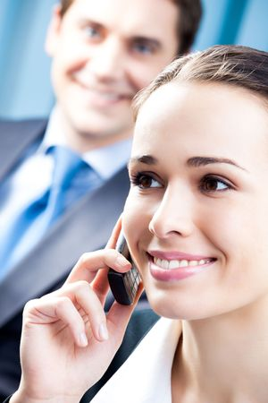 Successful businesswoman with cellphone and colleague, at office Stock Photo - 7486580