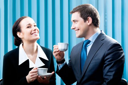 woman drinking coffee: Two happy businesspeople with coffee at office Stock Photo