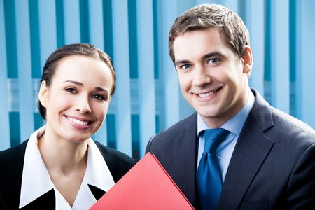 Two happy businesspeople with folder at office Stock Photo