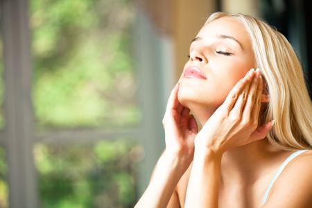 facial cream: Young beautiful smiling woman applying creme