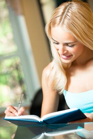 Young woman with notebook or organiser at home photo