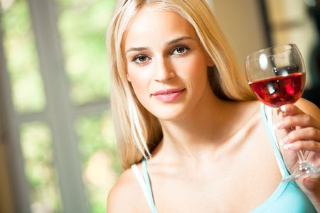 Young happy smiling woman with glass of red wine photo