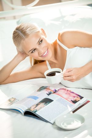 read magazine: Young woman reading a magazine at bedroom Stock Photo