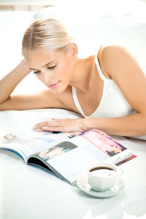 leggere rivista: Giovane donna leggendo una rivista in camera da letto