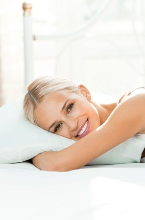 lay: Young happy smiling woman waking up at bedroom